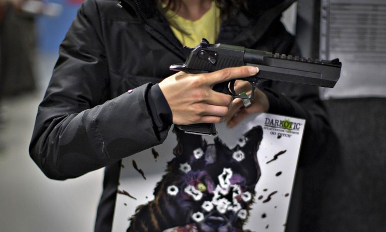 A woman holds a .50AE Desert Eagle and her target while visiting the DVC Indoor Shooting Centre in Port Coquitlam, British Columbia March 22, 2013. The centre has several kinds of pistols from 38 specials 44 magnums. (Andy Clark/REuters)