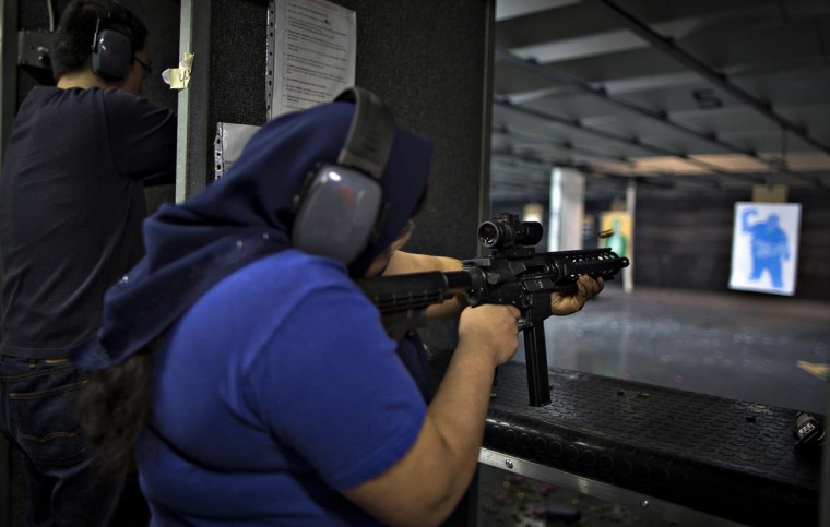 A woman fires a .22 calibre AR-15 rifle on the range at DVC Indoor Shooting Centre in Port Coquitlam, British Columbia March 22, 2013. (Andy Clark/Reuters)