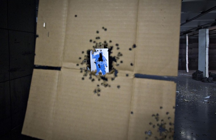 A target hit several times is seen through a piece of cardboard, also peppered with bullet holes, at the DVC Indoor Shooting Centre in Port Coquitlam, British Columbia March 22, 2013. The DVC is the only indoor shooting centre in the province that rents firearms to the public without a license. Canada has very strict laws controlling the use of handguns and violent crime is relatively rare. (Andy Clark/Reuters)