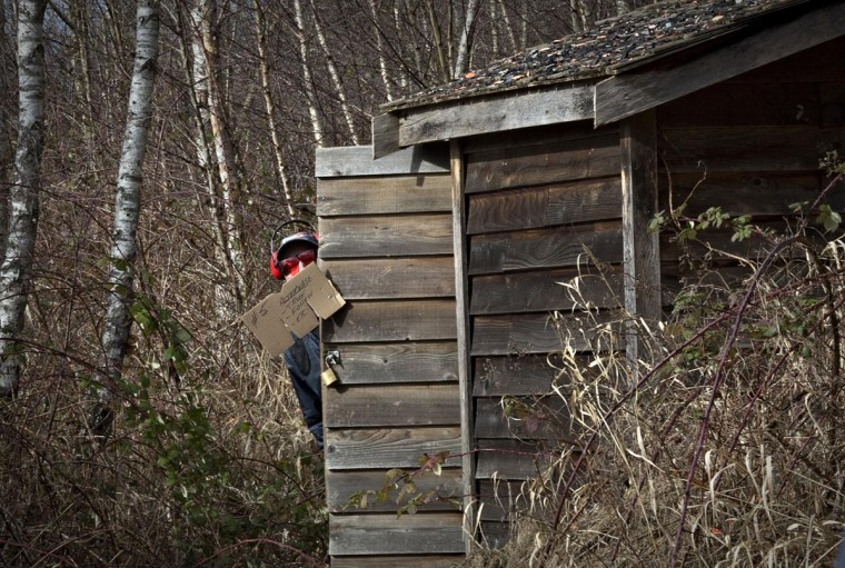 A member of the Vancouver Gun Club peeks out from behind the hut where sporting clays are fired from at the club's facility in Richmond, British Columbia February 17, 2013. (Andy Clark/Reuters)