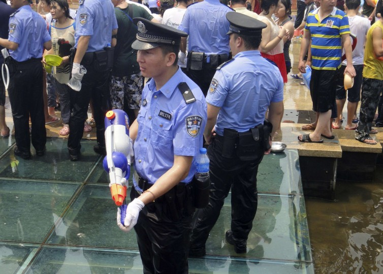 A policeman picks up a water gun which was left on the ground during the annual water-splashing festival to mark the New Year of the Dai minority in Xishuang Banna, Yunnan province . (Xishuang Banna/Reuters)