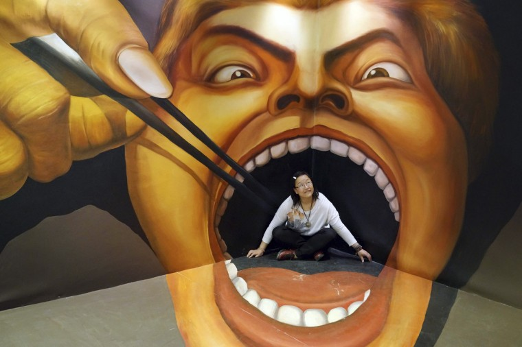 A woman poses for a photograph in front of a 3D painting at an exhibition in Guiyang, Guizhou province. (Reuters photo)