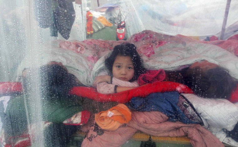 A girl (C) looks out from a makeshift tent during rainy weather as she sleeps with her family after Saturday's earthquake, in Lingguan town in Baoxing county, Sichuan province. The 6.6 magnitude quake struck in Lushan county, near the city of Ya'an in the southwestern province of Sichuan, close to where a devastating 7.9 quake hit in May 2008, killing 70,000. (Stringer/Reuters)