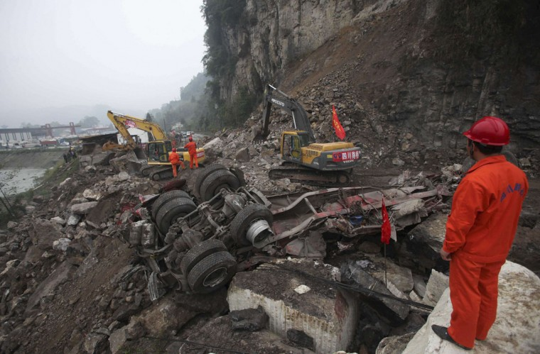 A rescuer looks on as excavators clean up a road which is blocked by a landslide after Saturday's earthquake, in Baoxing county, Sichuan province. The death toll has risen to at least 188, with more than 11,000 others injured, after an earthquake struck in Lushan county, near the city of Ya'an in the southwestern province of Sichuan on Saturday, Xinhua News Agency reported. (China Daily/Reuters)