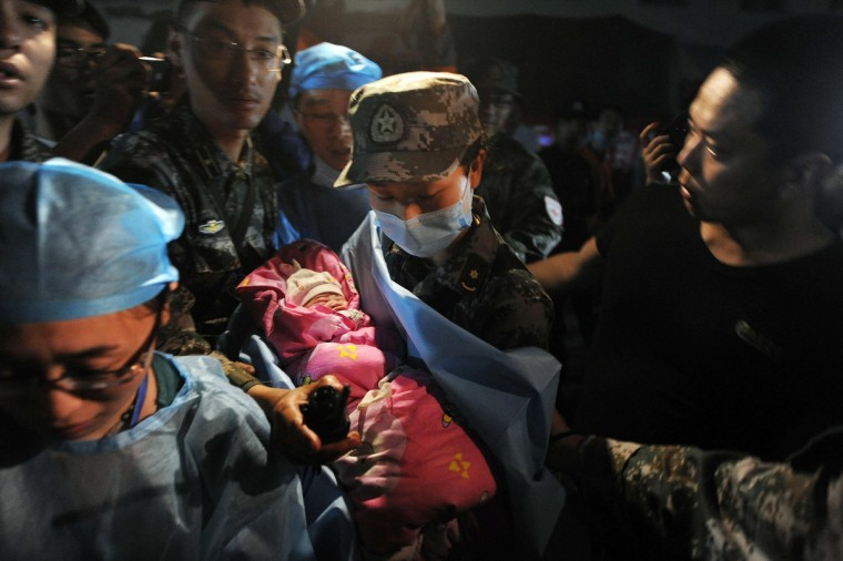 """A new-born baby which was born in a relief tent is attended by medical staff after Saturday's earthquake hit Lushan county, Ya'an, Sichuan province. Hundreds of survivors of an earthquake that killed nearly 200 people in southwest China pushed into traffic on a main road on Monday, waving protest signs, demanding help and shouting at police. The Chinese characters on the tent read """"Disaster relief"""". (Reuters)"""