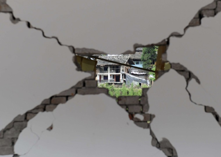 A damaged house is seen through a hole on a wall at Taiping township, Lushan county, Sichuan province. The earthquake so far left 196 dead, 21 missing and 11,470 injured, according to Xinhua News Agency. (China Daily/via Reuters)