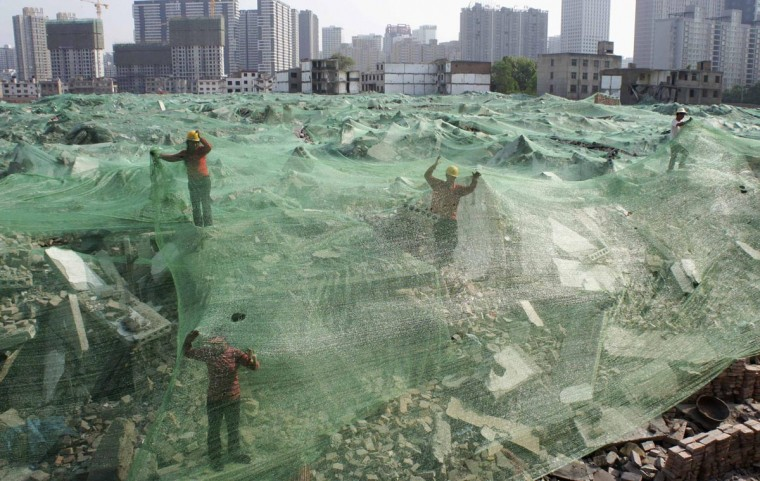 Workers set up dust screen on a demolition site in Xi'an, Shaanxi province, April 27, 2013. According to local media, along with the city's recent environment protection acts, construction sites are required to take measures controlling dust in order to improve air quality. Picture taken April 27, 2013. (Stringer/Reuters)