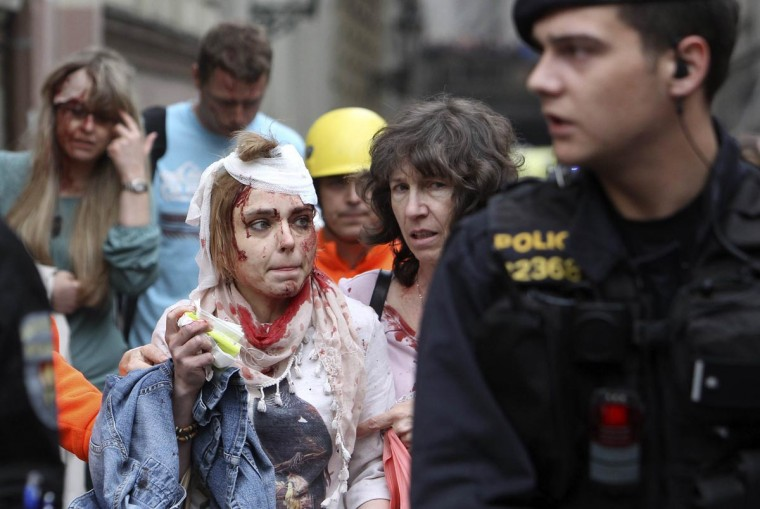 Injured people leave an area after an explosion in Prague April 29, 2013. The explosion in central Prague on Monday injured about a dozen people and others were trapped in a building damaged by the blast, a Reuters witness and emergency services officials said. (David W Cerny /Reuters)