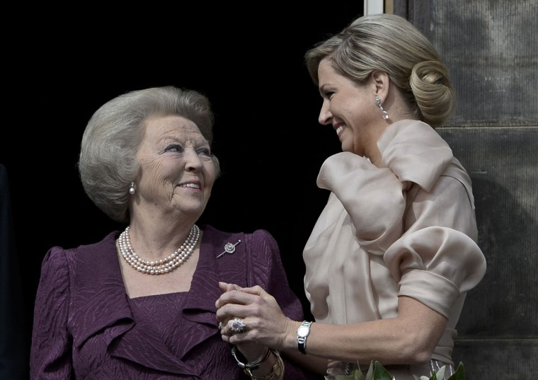 Queen Maxima, right, holds the hand of Princess Beatrix at the balcony of the Royal Palace in Amsterdam. The Netherlands is celebrating Queen's Day on Tuesday, which will also mark the abdication of Queen Beatrix and the investiture of her eldest son Willem-Alexander. (Dylan Martinez/Reuters)