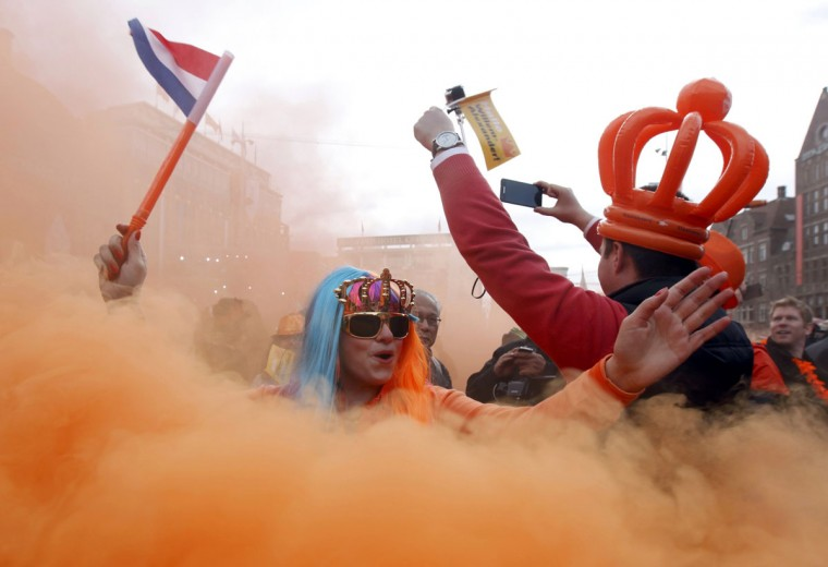 A woman celebrates the new Dutch King Willem-Alexander who succeeds his mother Queen Beatrix, in Amsterdam's Dam Square. (Cris Toala Olivares/Reuters)