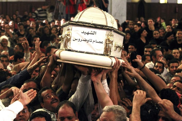 Coptic Orthodox Christians carry the coffins of men who died in clashes between Muslims and Christians in El Khusus north of the Egyptian capital, during their funeral at the main cathedral in Cairo April 7, 2013. Five Egyptians were killed and eight wounded in clashes between Christians and Muslims in the town near Cairo, security sources said on Saturday, in some of the worst sectarian violence in Egypt for months. (Mohamed Abd El Ghany/Reuters)