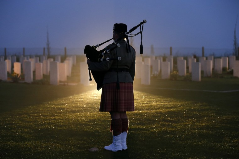 A man plays the bagpipes in a cemetery during the dawn service to mark the 98th ANZAC (Australian and New Zealand Army Corps) commemoration ceremony at the Australian National Memorial in Villers-Bretonneux, northern France. (Benoit Tessier/Reuters photo)