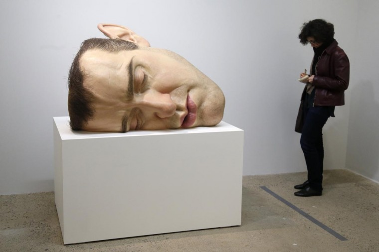 "A visitor looks at a sculpture entitled ""Mask II"" (2002) by artist Ron Mueck during the press day for his exhibition at the Fondation Cartier pour l'art contemporain in Paris April 15, 2013. The exhibition will run from April 16 to September 29, 2013. (Charles Platiau/Reuters)"