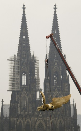 The 'Fluegelauto' (winged car) by German artist HA Schult is lowered by a crane to the top of Cologne's historic armoury. The Fluegelauto, a 1989 Ford Fiesta, returned to the roof of Cologne's city museum on Thursday in front of the famous Cologne cathedral after it has been renovated by the trainees of car maker Ford at its Cologne car plant. (Wolfgang Rattay/Reuters photo)