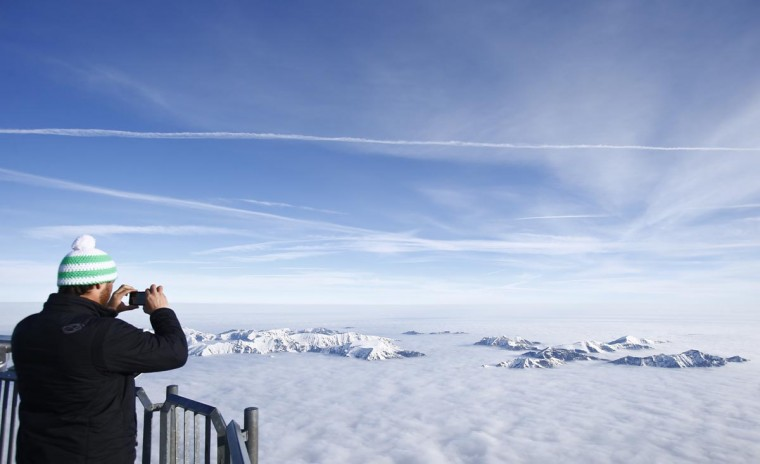 A man takes a picture of fog covered mountain summits, from Germany's highest mountain the 9,718 feet Zugspitze, on a sunny Spring day in the Bavarian village of Grainau April 3, 2012. (Dominic Ebenbichler/Reuters)
