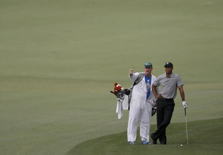 Tiger Woods of the U.S. (R) discusses his approach shot the second green with caddie Joe LaCava during first round play in the 2013 Masters golf tournament at the Augusta National Golf Club in Augusta, Georgia, April 11, 2013. (Phil Noble/Reuters)
