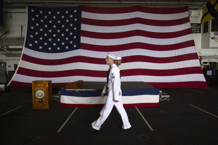 U.S. Navy personnels walk in front of a U.S flag in the amphibious assault ship USS Peleliu (LHA 5) as it docks at Tsim Sha Tsui for routine port visit in Hong Kong April 15, 2013. (Tyrone Siu/Reuters)