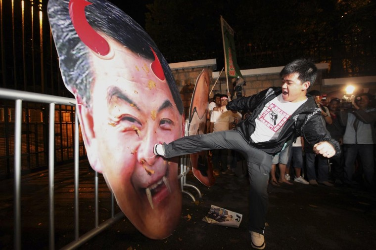 A protester in support of dock workers kicks a defaced portrait of Hong Kong Chief Executive Leung Chun-ying, outside his residency, in Hong Kong April 26, 2013. More than 200 dock workers have been on strike for four weeks for a pay rise at a port operated by tycoon Li Ka-shing, which has disrupted traffic in the world's third-largest container port. (Stringer/Reuters)