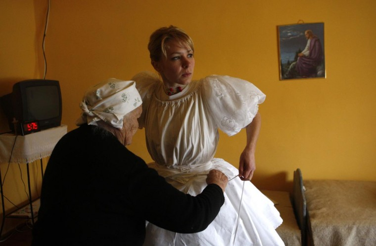 "A woman prepares for traditional Easter celebrations in Holloko, 62 miles east of Budapest on April 1, 2013. Locals from the World Heritage village of Holloko celebrate Easter with the traditional ""watering of the girls"", a Hungarian tribal fertility ritual rooted in the area's pre-Christian past. (Bernadett Szabo/Reuters)"