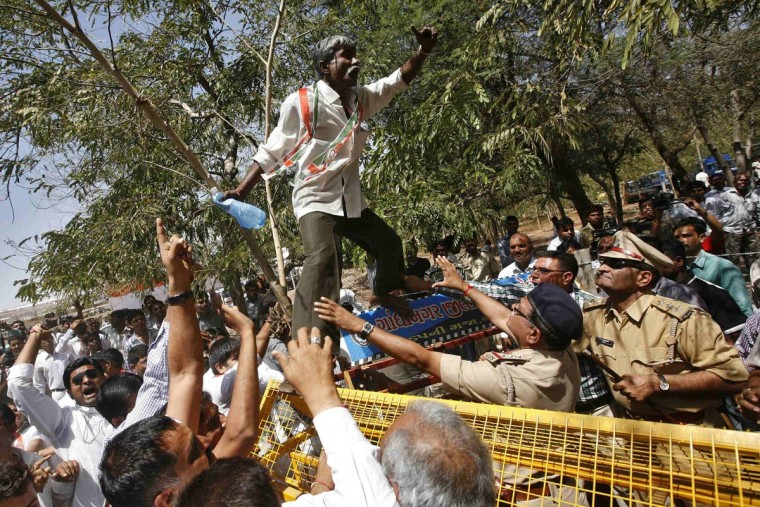 An activist from Congress party shouts as he stands on a police barricade during a protest at Gandhinagar, in the western Indian state of Gujarat, April 1, 2013. Hundreds of activists from Congress party and farmers held a protest on Monday demanding 12-hour electricity supply for farmers and a roll back of the Gujarat Irrigation and Drainage Bill that was passed by the state's ruling Bharatiya Janata Party (BJP) government recently, according to a media release by the protesters. (Amit Dave/Reuters)