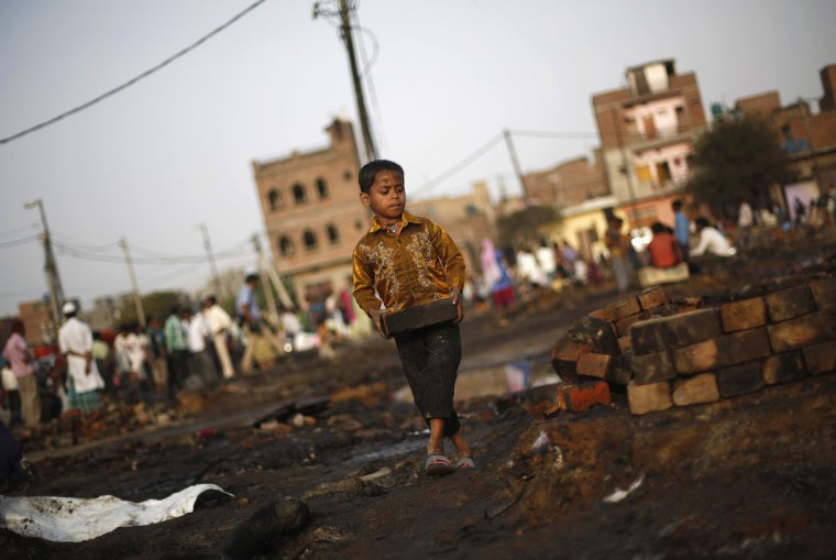 A boy carries a charred brick to build the boundary wall of his burnt hut after a fire broke out in a slum area in New Delhi. Two people including a child, died on Friday after a fire broke out in the slum area on the outskirts of Delhi gutting several huts, local media reported. (Adnan Abidi/Reuters)