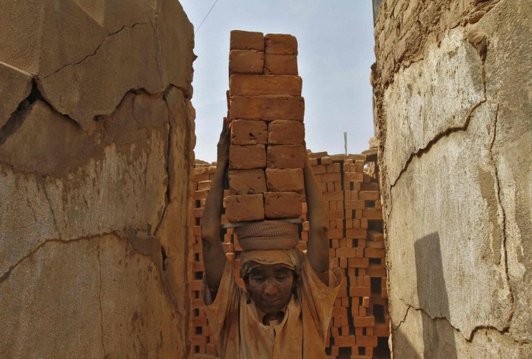 A female laborer carries bricks at a brick factory on the outskirts of the southern Indian city of Chennai. May Day or Labor Day will be marked on Wednesday. (Babu/Reuters)