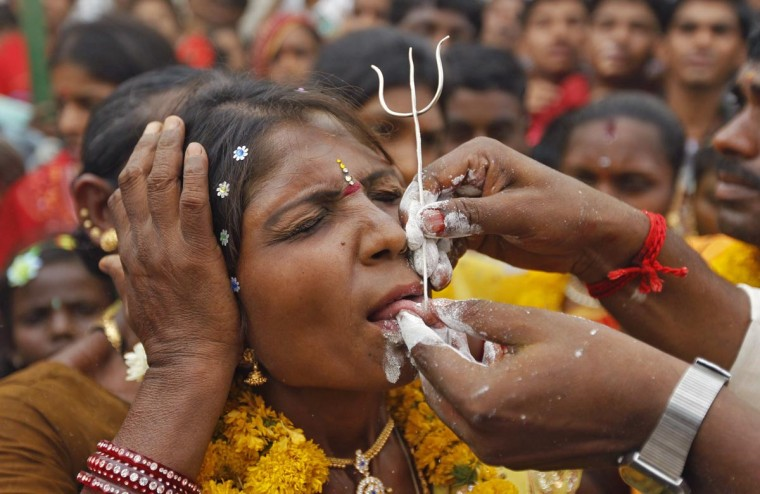 A Hindu devotee gets her tongue pierced with a trident as she takes part in an annual religious procession called Shitla Mata in the western Indian city of Ahmedabad April 29, 2013. Hindu devotees subject themselves to painful rituals during the religious procession to demonstrate their faith and as a penance to the deity at a temple dedicated to the goddess Shitla. (Amit Dave/Reuters)