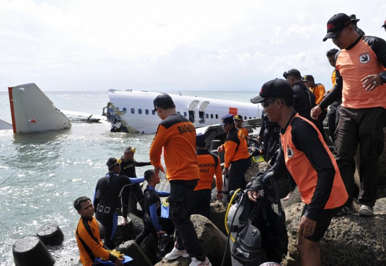 "A rescue team stands on the breakwater near a wreckage of a Lion Air plane near Ngurah Rai airport in Denpasar, Bali, April 15, 2013. The pilot whose Indonesian jet slumped into the sea while trying to land in Bali has described how he felt it ""dragged"" down by wind while he struggled to regain control, a person familiar with the matter said. (Stringer/Reuters)"