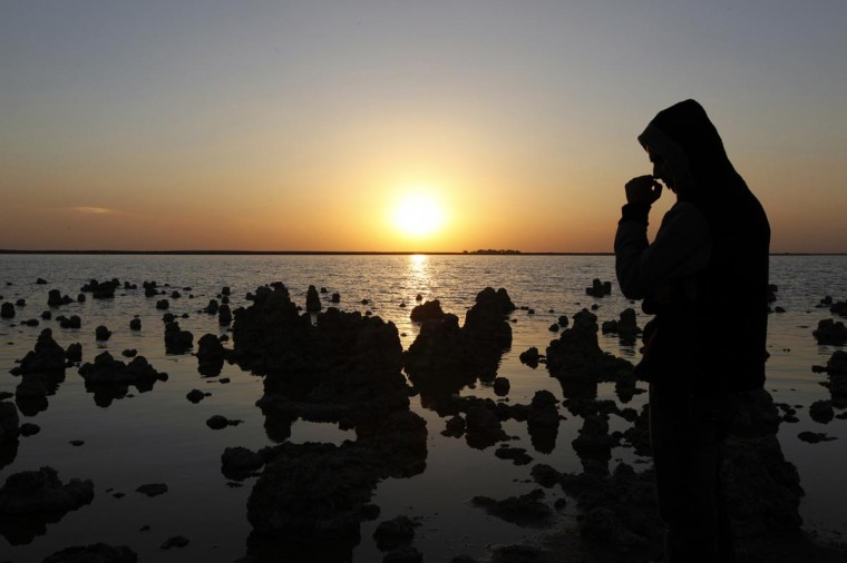 "A man stands next to Sawa lake in Samawa, 160 miles south of Baghdad February 22, 2013. One of the most well-known lakes in Iraq, Lake Sawa, is a large closed body of salt water situated in the desert between Baghdad and Basra. The lake is dubbed by some as ""the Pearl of the South"" for its beauty and unique composition. It is surrounded by a cliff of piled sand dunes, providing a natural levee that keeps the water above ground level. As the lake has no proven link to either river or sea, the source of its water has been a mystery to researchers for centuries. (Mohammed Ameen/Reuters)"