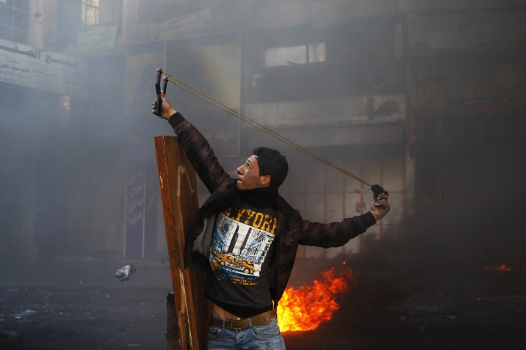 A Palestinian protester uses a slingshot to throw a stone during clashes with Israeli soldiers following the funeral of Maysara Abu Hamdeya in the West Bank city of Hebron. (Mussa Qawasma/Reuters photo)
