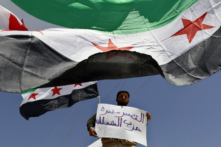 "A Syrian refugee holds a sign while standing under Syrian opposition flags during a protest to demand for the reinstatement of Moaz al-Khatib as head of the opposition Syrian National Coalition, and the setting of a buffer zone inside Syria, at Al Zaatri refugee camp in the Jordanian city of Mafraq, near the border with Syria. The sign reads: ""Al Qasyr it's a cemetery of the Satan party"". (Muhammad Hamed/Reuters photo)"