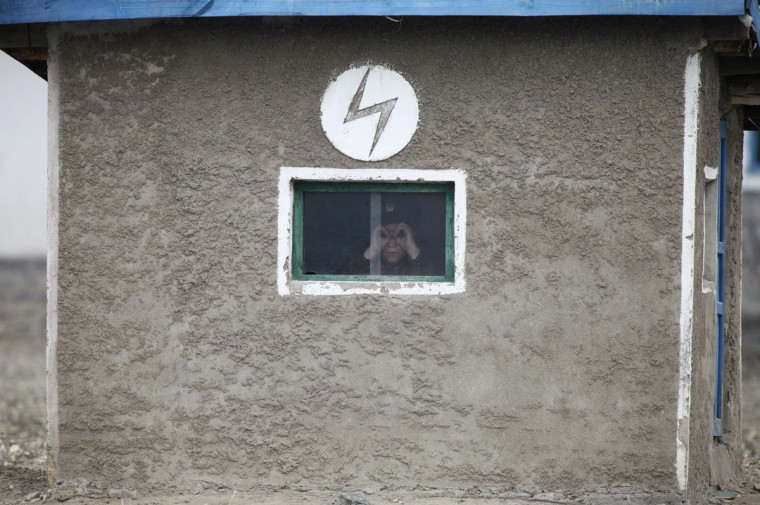 """A North Korean soldier looks out of the window of a guard tower, on the banks of Yalu River, about 100 km (62 miles) from the North Korean town of Sinuiju, opposite the Chinese border city of Dandong. North Korea issued new threats against South Korea on Tuesday, vowing """"sledge-hammer blows"""" of retaliation if South Korea did not apologise for anti-North Korean protests the previous day when the North was celebrating the birth of its founding leader. (Jacky Chen/Reuters)"""
