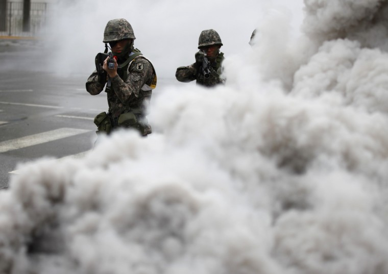 "South Korean soldiers walk through smoke as they take part in an anti-terror and security drill at the Integrated Government Complex in Sejong, south of Seoul. North Korea issued new threats against South Korea on Tuesday, vowing ""sledge-hammer blows"" of retaliation if South Korea did not apologize for anti-North Korean protests the previous day when the North was celebrating the birth of its founding leader. (Kim Hong-Ji/Reuters)"