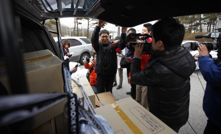 Reporters question a South Korean employee (C) as he returns from the KIC (Kaesong industrial complex) with products made in the KIC, at the South's CIQ (Customs, Immigration and Quarantine), just south of the demilitarised zone separating the two Koreas, in Paju, north of Seoul April 10, 2013. South Korea