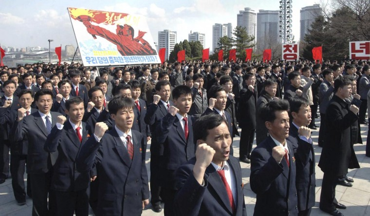 "People take part in an oath-taking meeting before the statues of late North Korean leaders Kim Il-sung and Kim Jong-il on Mansudae Hill in Pyongyang April 10, 2013 in this photo distributed by North Korea's Korean Central News Agency (KCNA). Sign reads: ""Let's become faithful youth vanguard of our party!"" (KCNA via Reuters)"