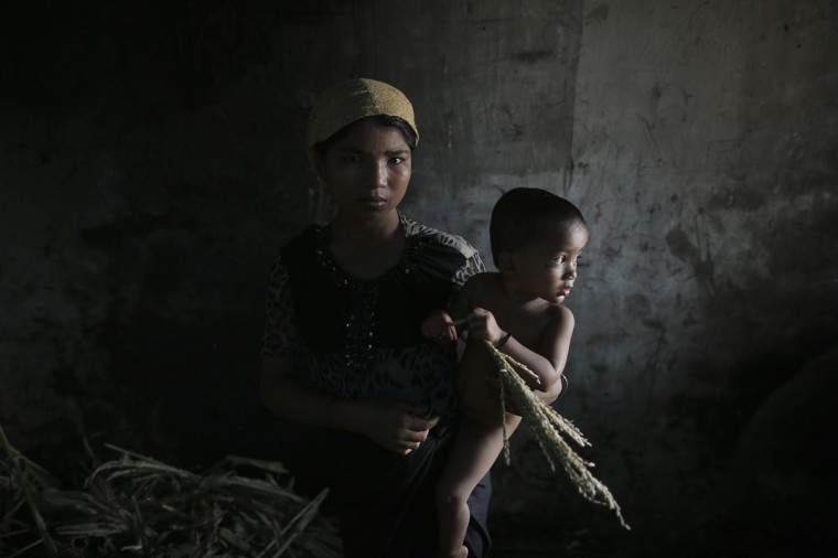 Hla Hla May, a Rohingya Muslim woman displaced by violence, holds her one year old daughter Roshan at a former rubber factory that now serves as their shelter, near Sittwe April 29, 2013. Myanmar must urgently address the plight of Muslims displaced by sectarian bloodshed in western Rakhine State and double the number of security forces to control the still-volatile region, an independent commission said on Monday. (Damir Sagolj/Reuters)