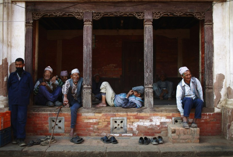 Men pass their time sitting along a street in Bhaktapur, Nepal. (Navesh Chitrakar/Reuters photo)