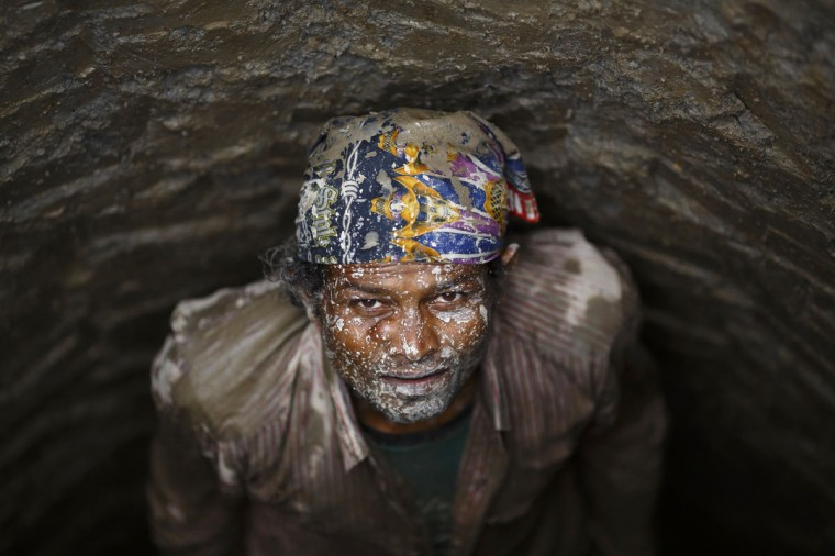 A man with face covered with mud looks up at his friends while constructing a well at Khokana, Lalitpur. (Navesh Chitrakar/Reuters)