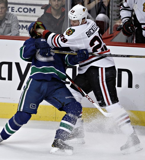 Chicago Blackhawks' Bryan Bickell (R) knocks Vancouver Canucks' Henrik Sedin over during the third period of their NHL hockey game in Vancouver, British Columbia. (Andy Clark/Reuters)