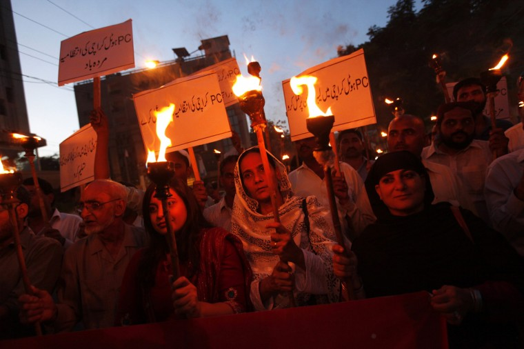 "Activists from various labour organizations take part in a torch-lit rally demanding improvements to working conditions, on the eve of International Labour Day or May Day, in Karachi . The sign (top L) reads in Urdu, ""Down with the management of PC hotel, Karachi"". (Akhtar Soomro/Reuters)"