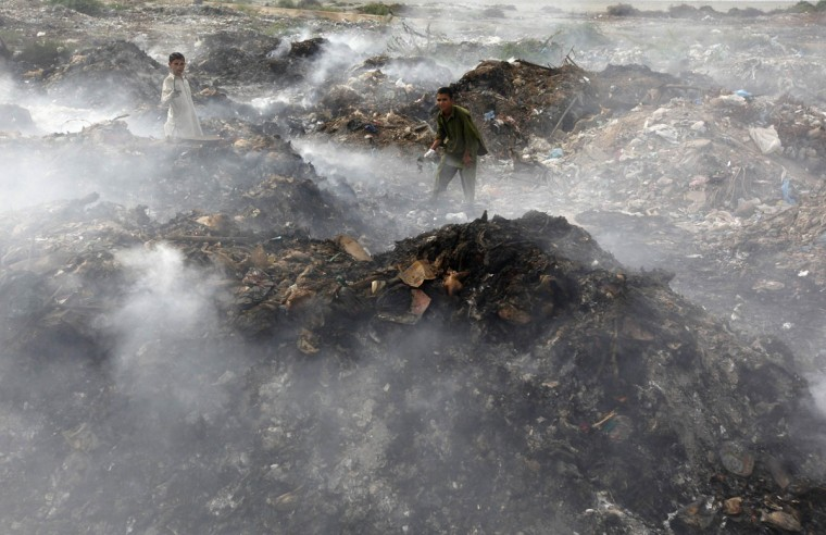 Boys collect recyclables from the pile of smouldering garbage dump on the outskirts of Karachi, Pakistan. (Akhtar Soomro/Reuters)