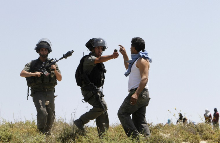 An Israeli border police officer aims pepper spray towards a Palestinian man during clashes between Jewish settlers and Palestinians in the West bank village of Urif, near Nablus. The clashes erupted after an attack near Nablus. A Palestinian man stabbed and shot dead an Israeli settler in the occupied West Bank on Tuesday, the Israeli ambulance service and police said.(Abed Omar Qusini/Reuters)