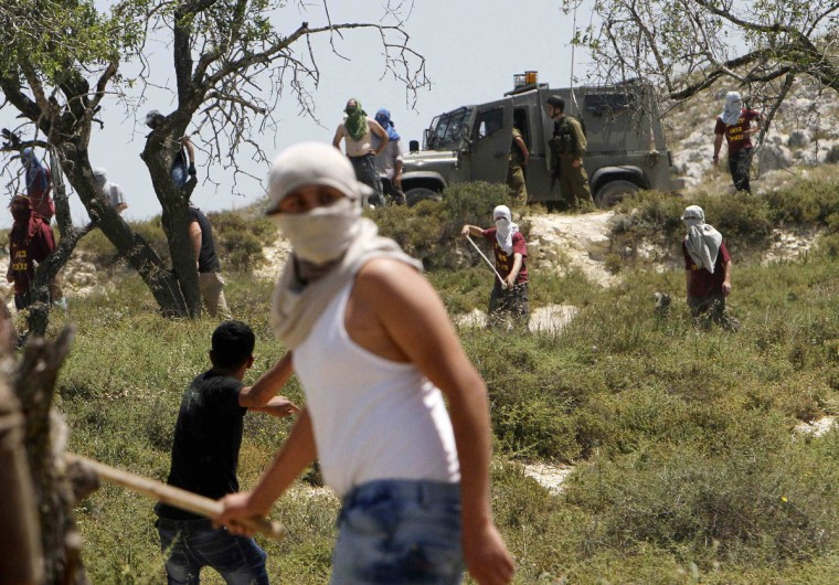 Stone-throwing Palestinians and Jewish settlers (background) clash near Israeli soldiers in the West Bank village of Urif, near Nablus. The clashes erupted after an attack near Nablus. A Palestinian man stabbed and shot dead an Israeli settler in the occupied West Bank on Tuesday, the Israeli ambulance service and police said. (Abed Omar Qusini/Reuters)