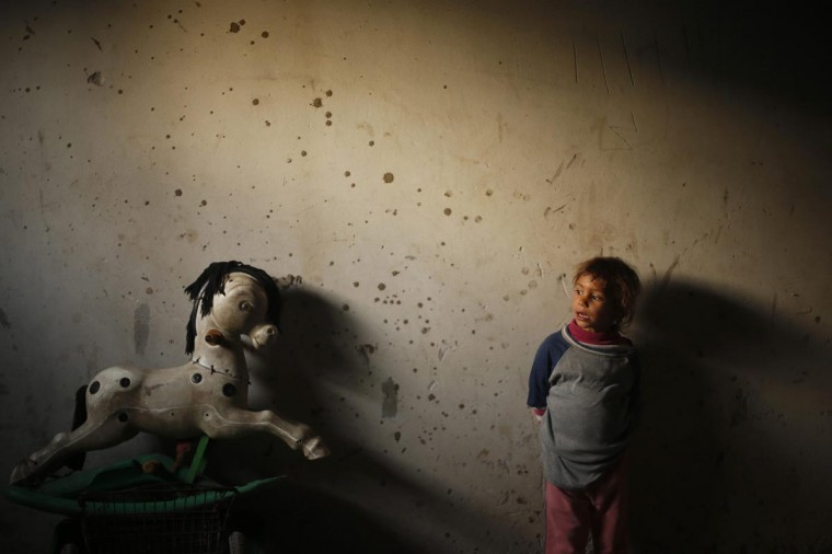A Palestinian girl looks on inside her family's damaged house in Beit Lahiya, near the border between Israel and northern Gaza Strip April 7, 2013. (Mohammed Salem/Reuters)