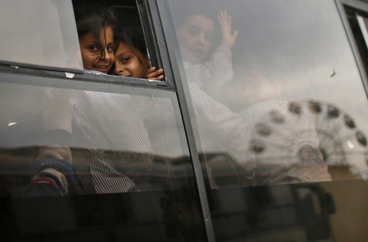 Palestinian school girls look through glass windows of a bus outside an amusement park built on a land of a former Israeli settlement in central Gaza Strip. (Mohammed Salem/Reuters photo)