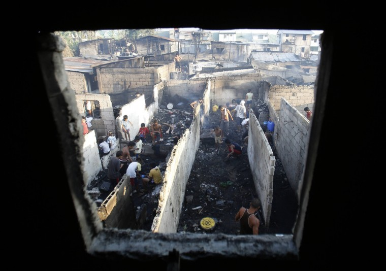 Residents are seen from a burnt window as they salvage from the burnt remains of their homes after a fire in Quezon City, Metro Manila. According to local media, at least one hundred houses were razed in the fire this morning, leaving two hundred families homeless and injuring three people. Investigators are still looking into the cause of the fire. (Cheryl Ravelo/Reuters)