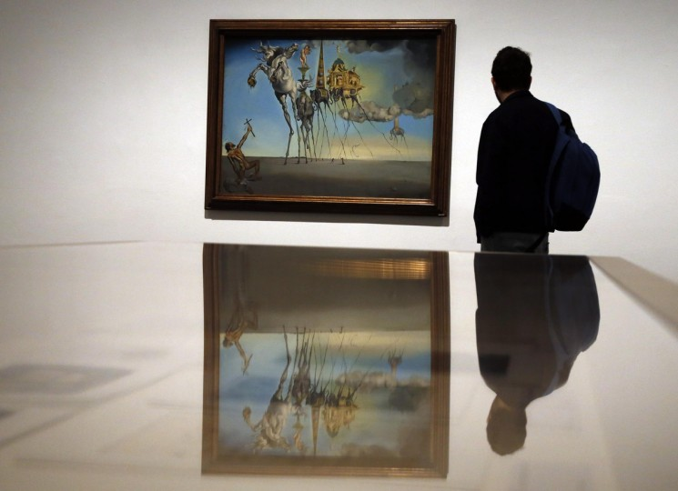 "A man looks at a painting titled ""La tentacion de San Antonio"" (""The Temptation of St. Anthony"") by Spanish artist Salvador Dali during a media preview of an exhibition at Reina Sofia museum in Madrid. The exhibition will run from April 27 to September 2. (Sergio Perez/Reuters photo)"