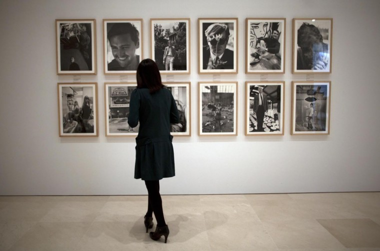 "A worker looks at photographs of the ""Dennis Hopper. On the road"" exhibition by artist Dennis Hopper during the inauguration at the Picasso Museum in Malaga, southern Spain April 29, 2013. The exhibition shows a total of 141 photographs from Dennis Hopper's photography legacy, most of them produced during the 1960s. (Jon Nazca/Reuters)"