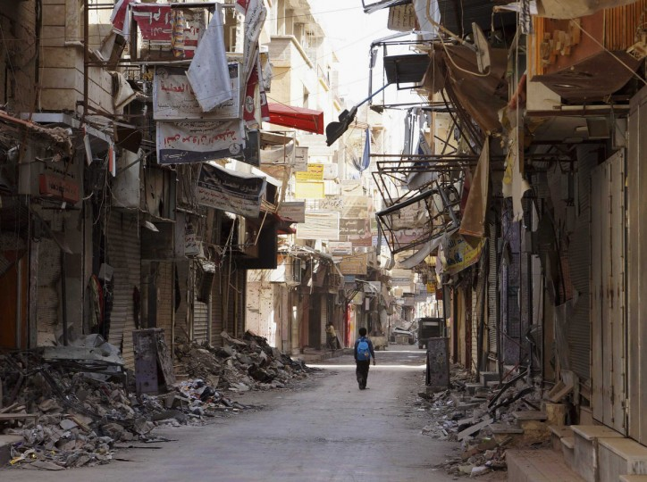A boy walks along a damaged street filled with debris in Deir al-Zor, Syria. (Khalil Ashawi/Reuters photo)