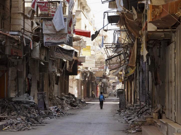 A boy walks along a damaged street filled with debris in Deir al-Zor, Syria. (Khalil Ashawi/Reuters photo)